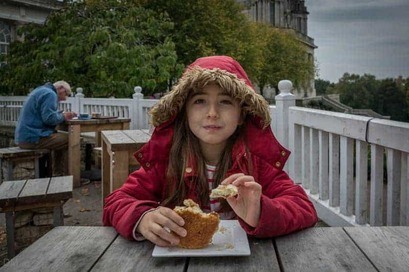 Girl eating a scone at the Pavilion Cafe at Williamson Park in Lancaster.