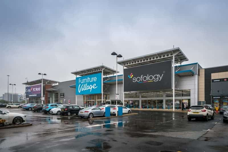 Currys PC World, Furniture Village, and Sofology stores at White City Retail Park in Manchester