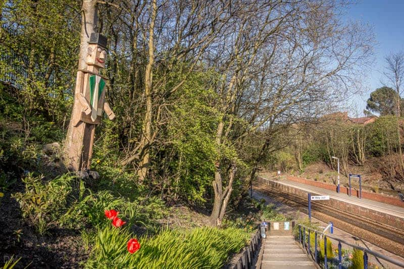 Station master and flower beds at the entrance to the northern platform of Westhoughton  Train Station