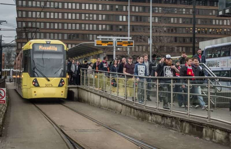 Manchester United fans getting off a tram at Piccadilly Gardens Metrolink Station