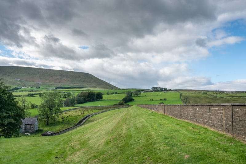 Embankment at Lower Black Moss Reservoir and view of Pendle Hill
