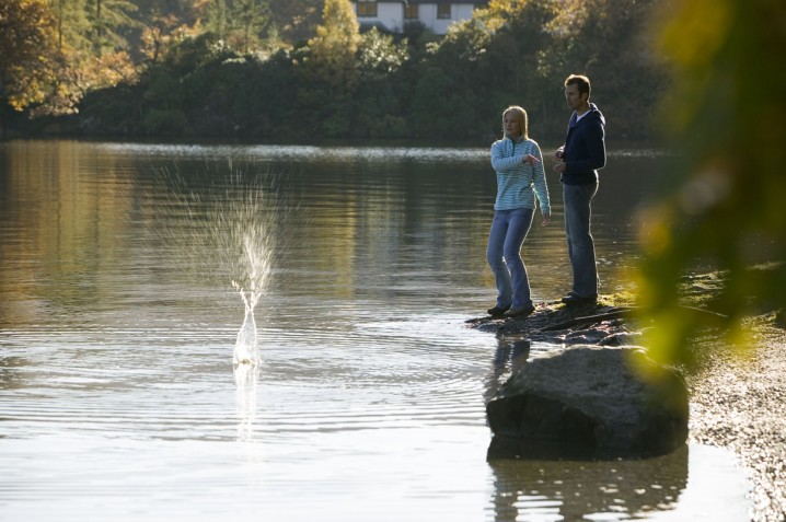 Couple throwing stones into Derwent Water in the Lake District, England