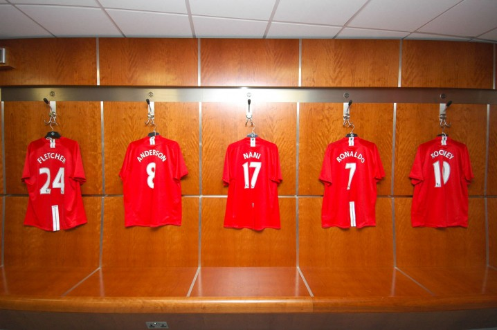 Dressing room at Old Trafford with players shirts hanging on the wall